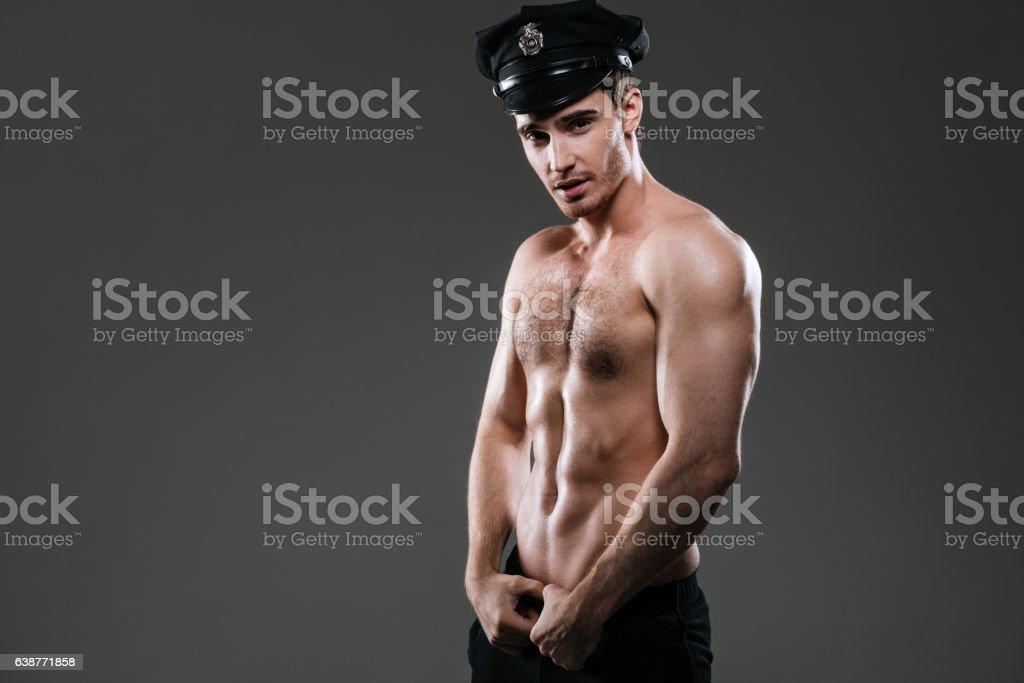 Stripper policeman wearing police hat. stock photo