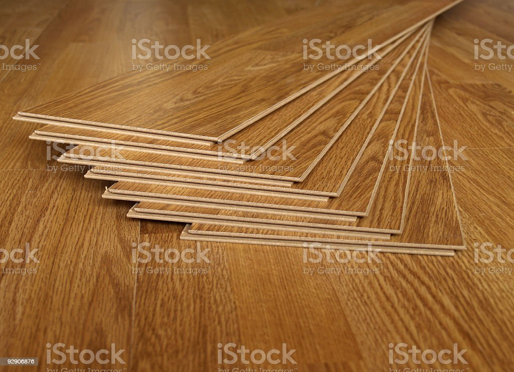 Strips of laminate flooring on top of a laid laminate floor stock photo