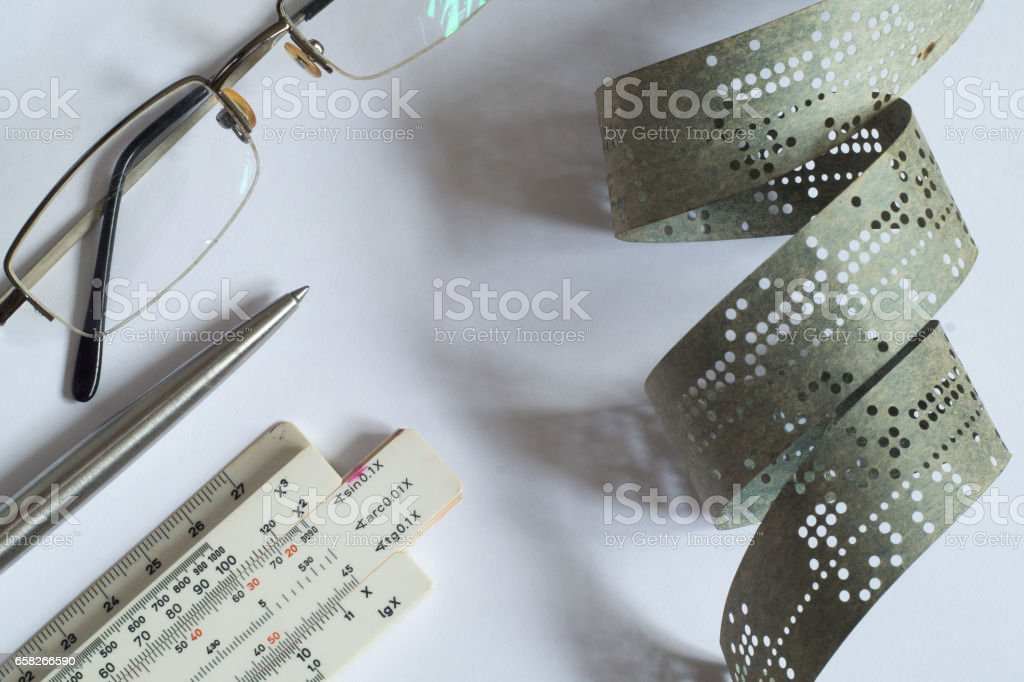 Strips of old punched tape on a white surface stock photo