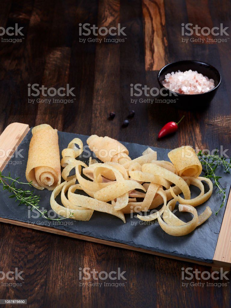 Strips of salted raw pork rind strips on a slate board stock photo
