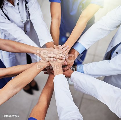Cropped shot of a team of doctors joining their hands together in unity