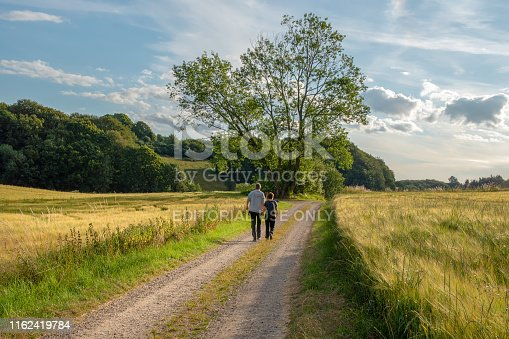 Skanderborg, Denmark; 16th July - Middle aged couple strolling along in the countryside.