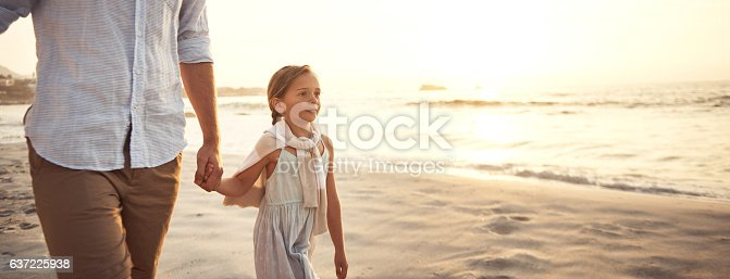 Shot of a father holding his little girl's hand as they walk on the beach at sunset
