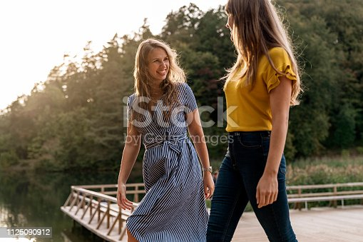 Contemporary young girlfriends walking on wooden pier of lake in sunlight and chatting