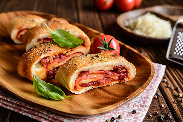 stromboli stuffed with cheese, salami, green onion and tomato sauce - savory food stock photos and pictures