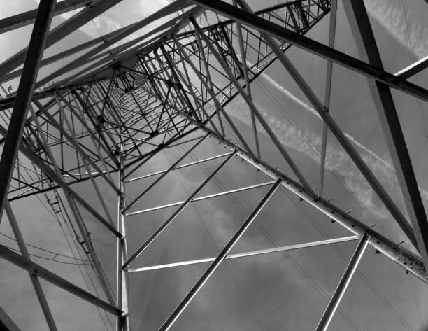 Strom-Masten aus Stahl in steiler Perspektive in Schwarz-Weiß UV-Filter, Fernleitung, Freileitung, Stromverteilung, Energietranspor, Starkstromleitung, Energiewirtschaft, fluchtpunktperspektive stock pictures, royalty-free photos & images
