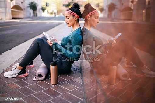 1091470492 istock photo Strong active woman sitting with her back against a marble building wall in a city street 1082375354