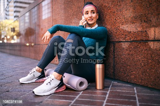 1091470492 istock photo Strong active woman talking on a mobile phone while sitting with her back against a marble building wall on a street sidewalk 1082374158