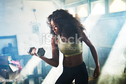 930998708 istock photo strong african american woman doing weight lifting dumbbells 930999578