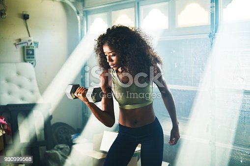 930998708 istock photo strong african american woman doing weight lifting 930999568