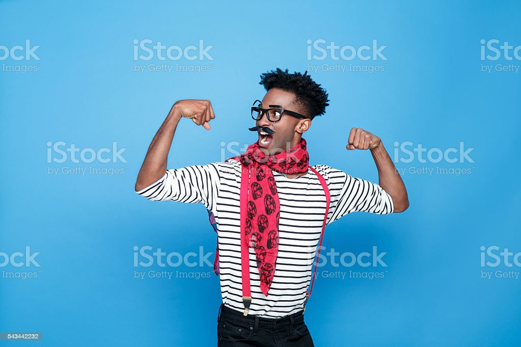 Strong afro american guy in a french outfit flexing bicep Portrait of excited afro american guy wearing striped long sleeved t-shirt, red suspenders and neckscarf, flexing his biceps. Studio shot, blue background.  Adult Stock Photo