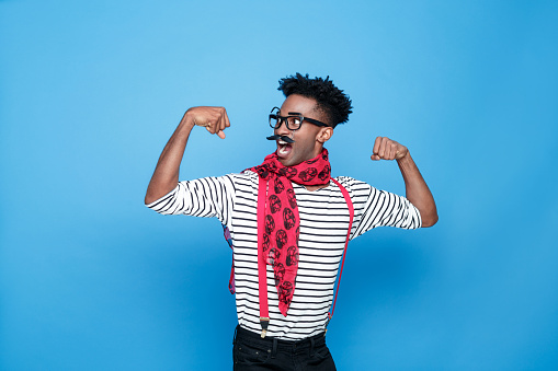 Strong Afro American Guy In A French Outfit Flexing Bicep Stock Photo - Download Image Now