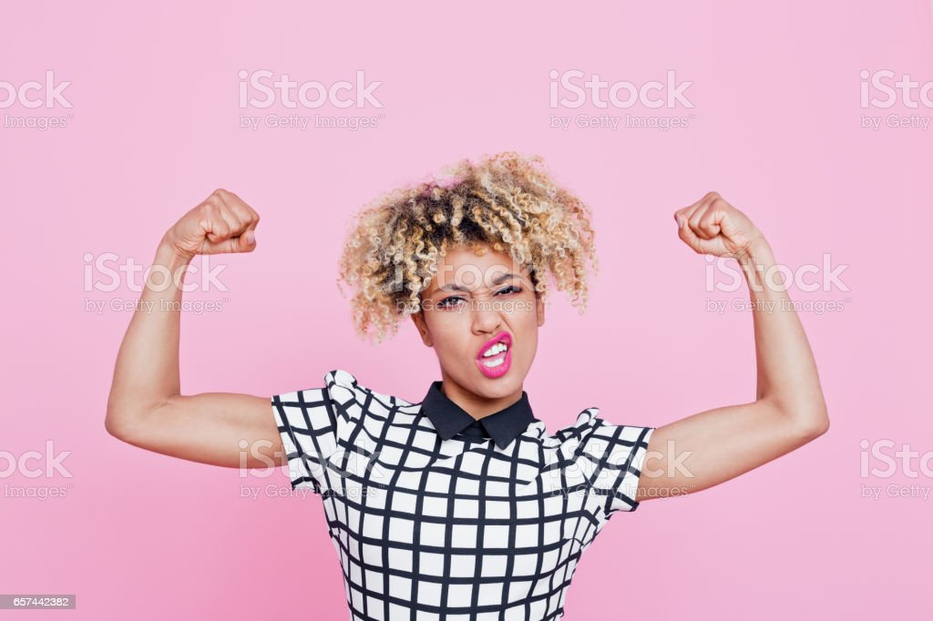 Strong afro american young woman flexing muscles Studio portrait of strong afro american young woman flexing muscles. Pink background. 20-24 Years Stock Photo