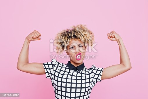 Studio portrait of strong afro american young woman flexing muscles. Pink background.