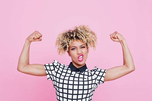 istock Strong afro american young woman flexing muscles 657442382