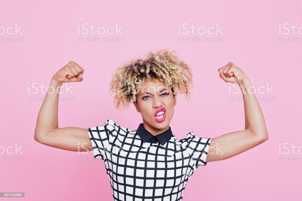 Afro americana jovem forte flexionando os músculos - foto de acervo