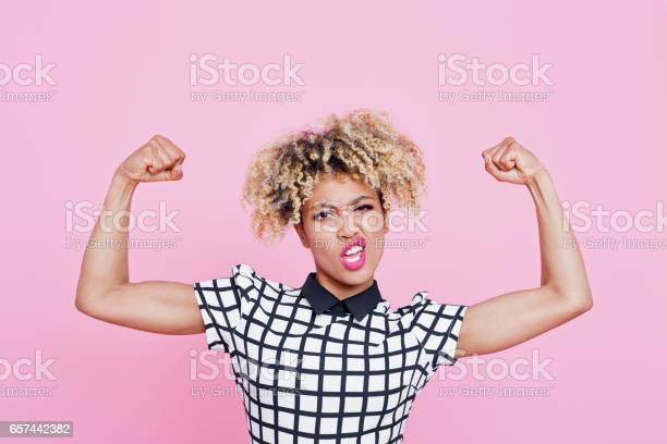 Strong Afro American Young Woman Flexing Muscles Stock Photo - Download Image Now