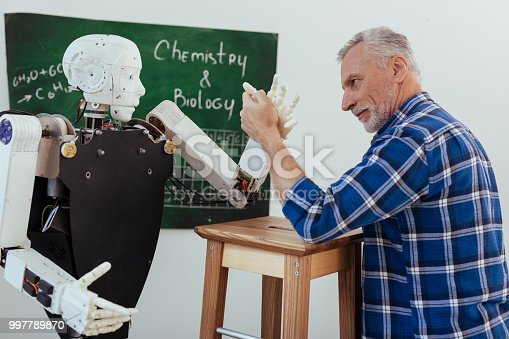 istock Strong aged man looking at the robot 997789870