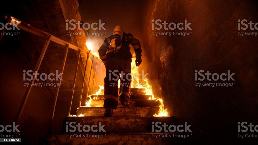 Forte e corajoso bombeiro indo Up The Stairs edifício ardente. Queimadura de escadas com chamas abertas. - foto de acervo