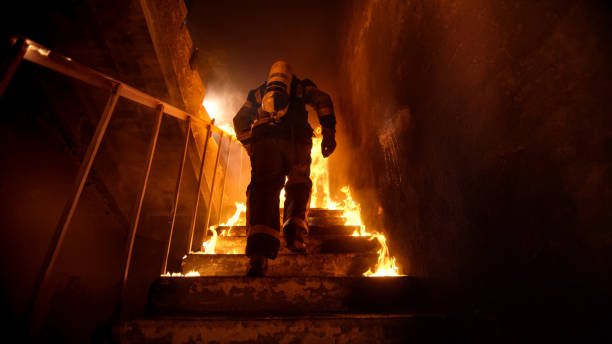 Strong and brave Firefighter Going Up The Stairs in Burning Building. Stairs Burn With Open Flames. stock photo
