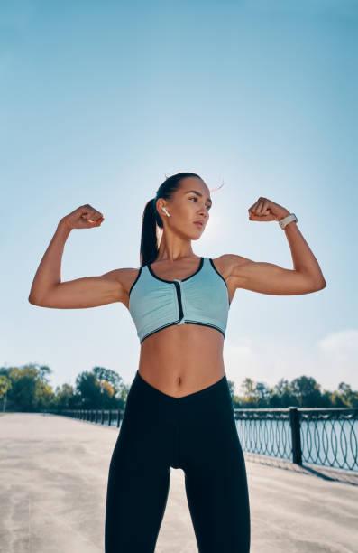Fuerte y segura hermosa mujer flexionando sus músculos - foto de stock