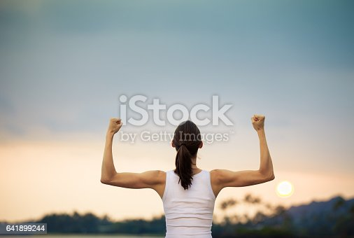 istock Strong and confident woman flexing her muscle. 641899244