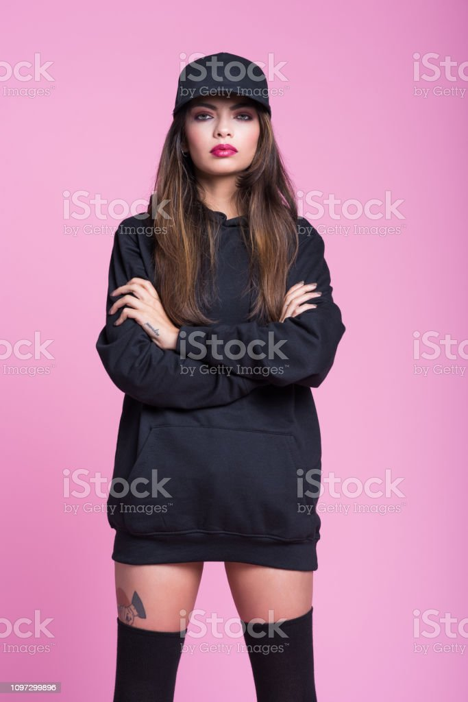 Studio portrait of strong young woman wearing black clothes and...