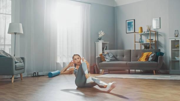 Starke und fit schöne Mädchen in einem grauen Athletik Outfit energetisch Übung in ihrem hellen und geräumigen Wohnzimmer mit minimalistischem Interieur. – Foto