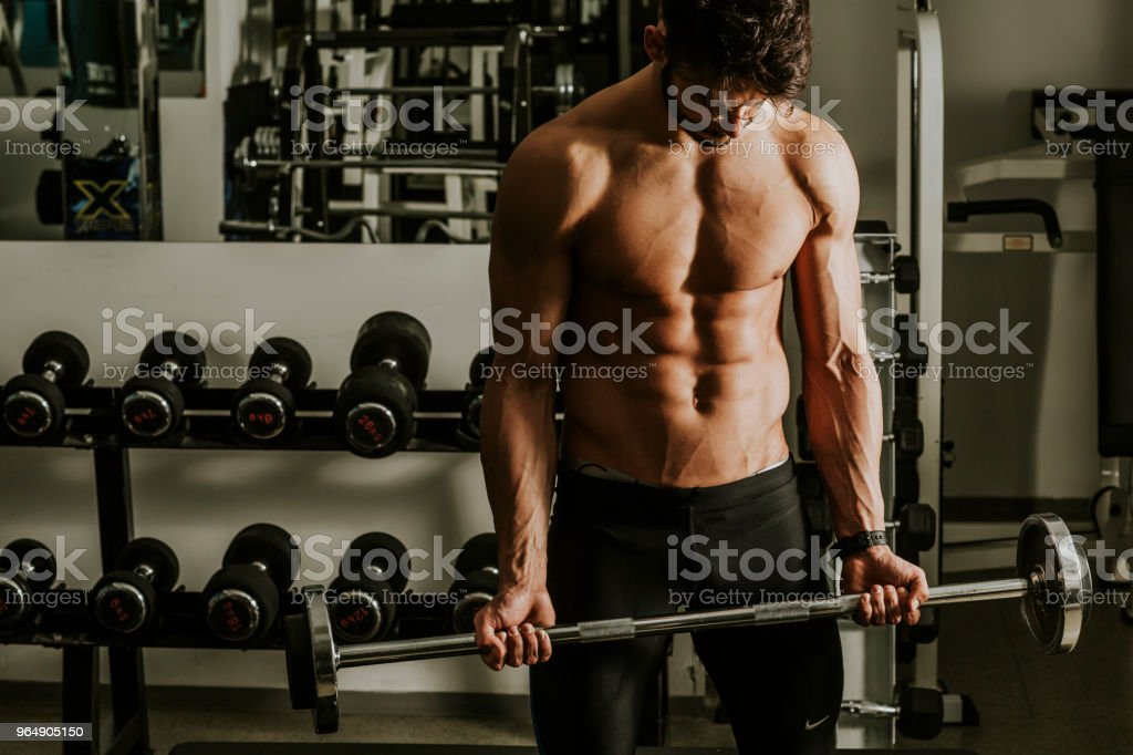 Strong and handsome young man doing exercise with dumbbells royalty-free stock photo
