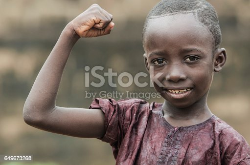 istock Strong and Proud Little African Boy Showing Off his muscles as a power symbol 649673268