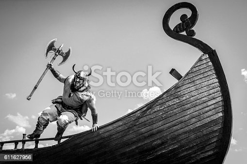 istock Strong angry bearded Viking with axe attacking. 611627956