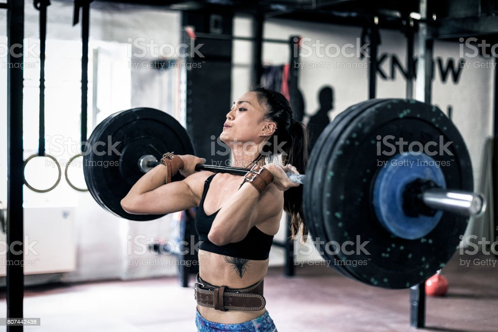Strong Asian woman lifting weights stock photo