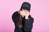 Angry young asian woman wearing black hooded shirt and baseball cap, hitting her fist towards camera. Studio shot, pink background.