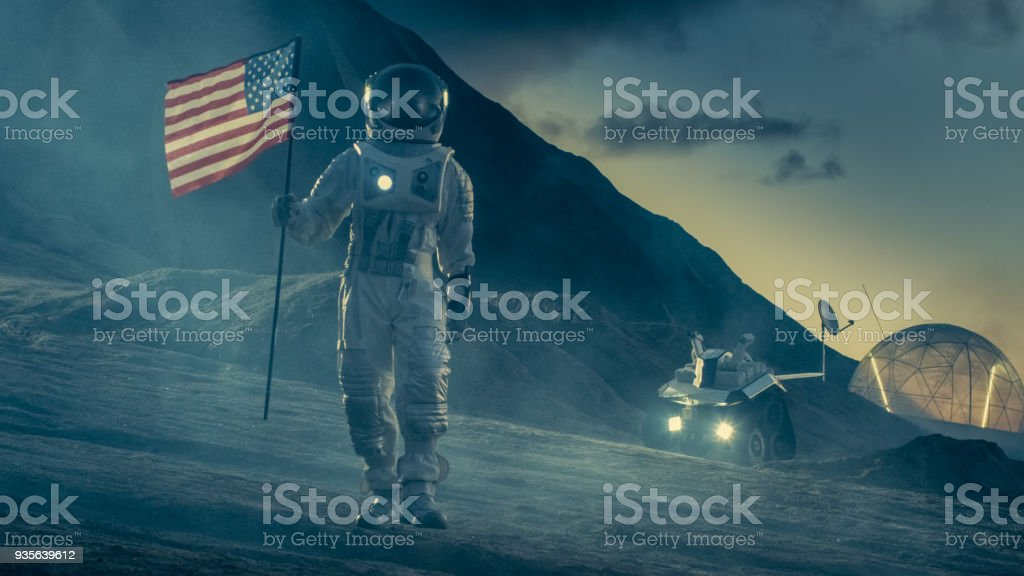 Strong Astronaut On Alien Planet Walks Through the Storm with a Flag of Unites States of America. In the Background His Research Base/ Station and Rover. Space Travel, Colonisation Theme. stock photo