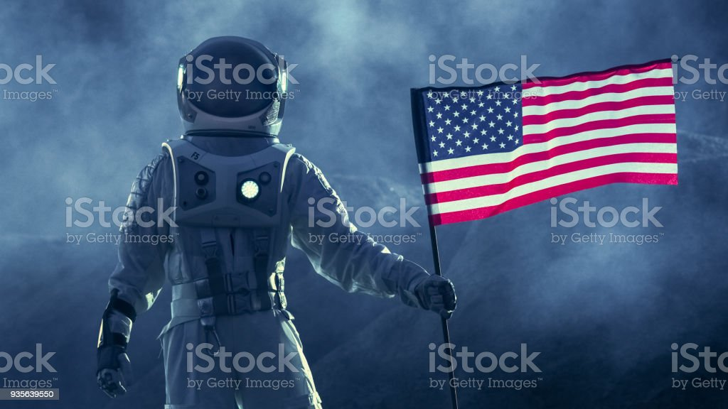 Strong Astronaut Walks Through the Storm with a Flag of Unites States of America, Proudly Pants it on the Dark Alien Planet. Space Travel, Colonisation Theme. stock photo