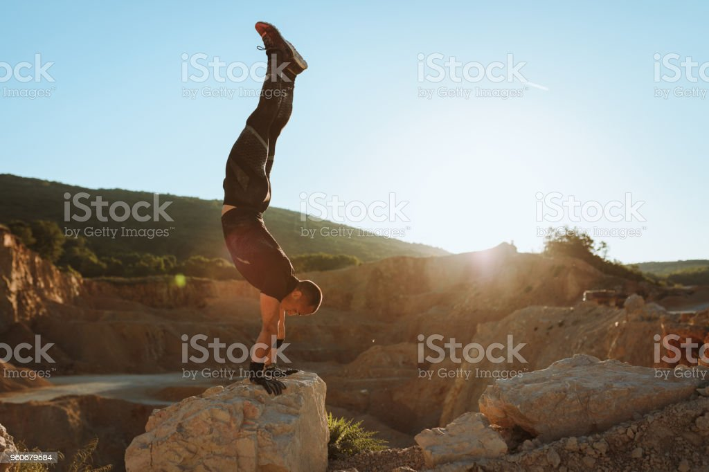 Strong athlete exercising on the top of the mountain stock photo