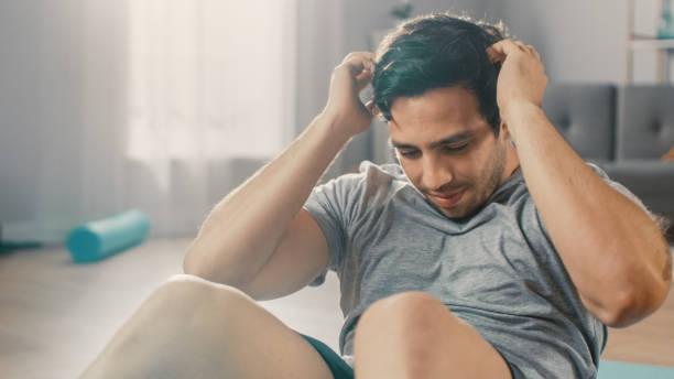 Strong Athletic Fit Man in T-Shirt und Shorts macht Abdominal Crunch Workout zu Hause in seinem geräumigen und hellen Wohnzimmer mit minimalistischem Interieur. – Foto