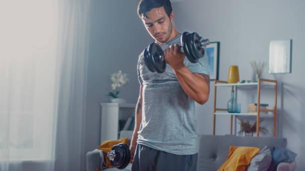 Strong Athletic Fit Man in T-shirt and Shorts is Doing Calf Raise Exercises with Dumbbells at Home in His Spacious and Bright Apartment with Minimalistic Interior. Strong Athletic Fit Man in T-shirt and Shorts is Doing Calf Raise Exercises with Dumbbells at Home in His Spacious and Bright Apartment with Minimalistic Interior. bicep stock pictures, royalty-free photos & images