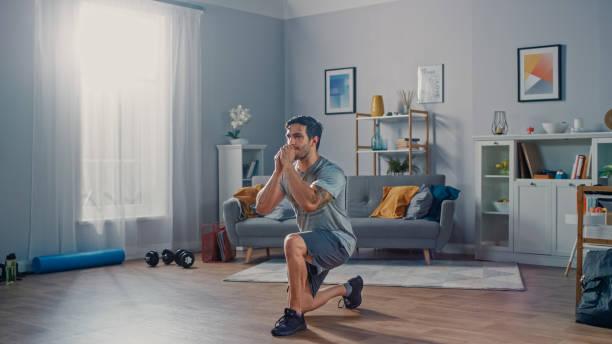 sterke atletische fit man in t-shirt en shorts doet vooruit lunge oefeningen thuis in zijn ruime en lichte appartement met minimalistisch interieur. - ontspanningsoefening stockfoto's en -beelden