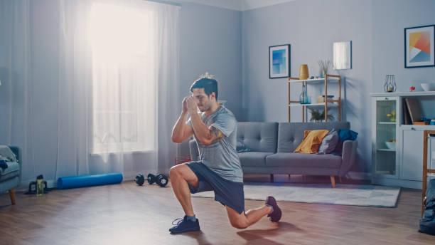 Strong Athletic Fit Man in T-shirt and Shorts is Doing Forward Lunge Exercises at Home in His Spacious and Bright Apartment with Minimalistic Interior. Strong Athletic Fit Man in T-shirt and Shorts is Doing Forward Lunge Exercises at Home in His Spacious and Bright Apartment with Minimalistic Interior. only young men stock pictures, royalty-free photos & images