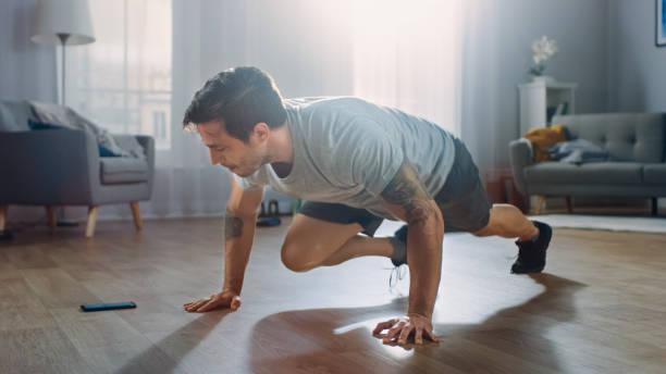 Strong Athletic Fit Mann in T-Shirt und Shorts macht Bergsteiger Übungen, während mit einer Stoppuhr auf seinem Handy. Er trainiert zu Hause in seiner geräumigen Wohnung mit minimalistischem Interieur. – Foto