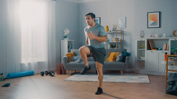 Strong Athletic Fit Man in T-shirt and Shorts is Energetically Jogging in Place at Home in His Spacious and Bright Living Room with Minimalistic Interior. Strong Athletic Fit Man in T-shirt and Shorts is Energetically Jogging in Place at Home in His Spacious and Bright Living Room with Minimalistic Interior. cardiovascular exercise stock pictures, royalty-free photos & images