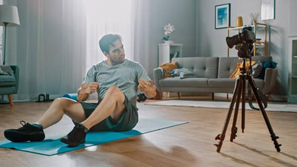 Strong Athletic Fit Man in T-Shirt und Shorts nimmt sein Workout vor der Kamera für seinen Blog auf. Szene spielt in seinem geräumigen und hellen Wohnzimmer mit minimalistischem Interieur. – Foto