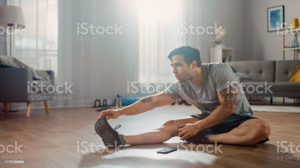 Strong Athletic Fit Man in T-shirt and Shorts Stretches His Body for Morning Exercises at Home in His Spacious and Bright Living Room with Minimalistic Interior. Strong Athletic Fit Man in T-shirt and Shorts Stretches His Body for Morning Exercises at Home in His Spacious and Bright Living Room with Minimalistic Interior. Abdominal Muscle Stock Photo