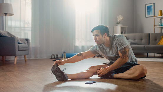Strong Athletic Fit Man In Tshirt And Shorts Stretches His Body For Morning Exercises At Home In His Spacious And Bright Living Room With Minimalistic Interior Stock Photo - Download Image Now