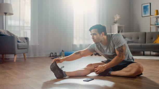 Strong Athletic Fit Man in T-Shirt und Shorts dehnt seinen Körper für Morgenübungen zu Hause in seinem geräumigen und hellen Wohnzimmer mit minimalistischem Interieur. – Foto