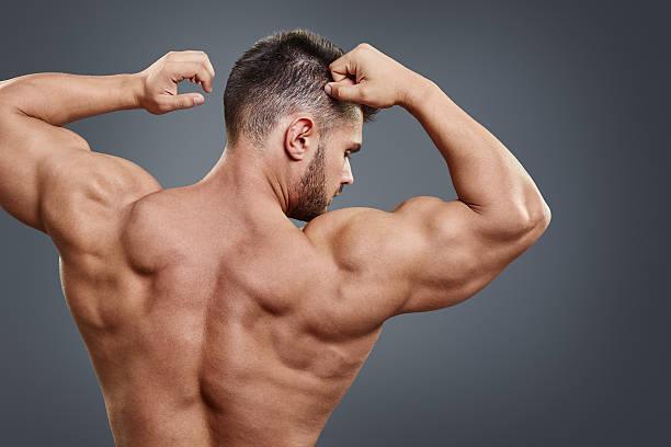 バックにアスレチックな男の灰色の背景 - 筋肉 ストックフォトと画像