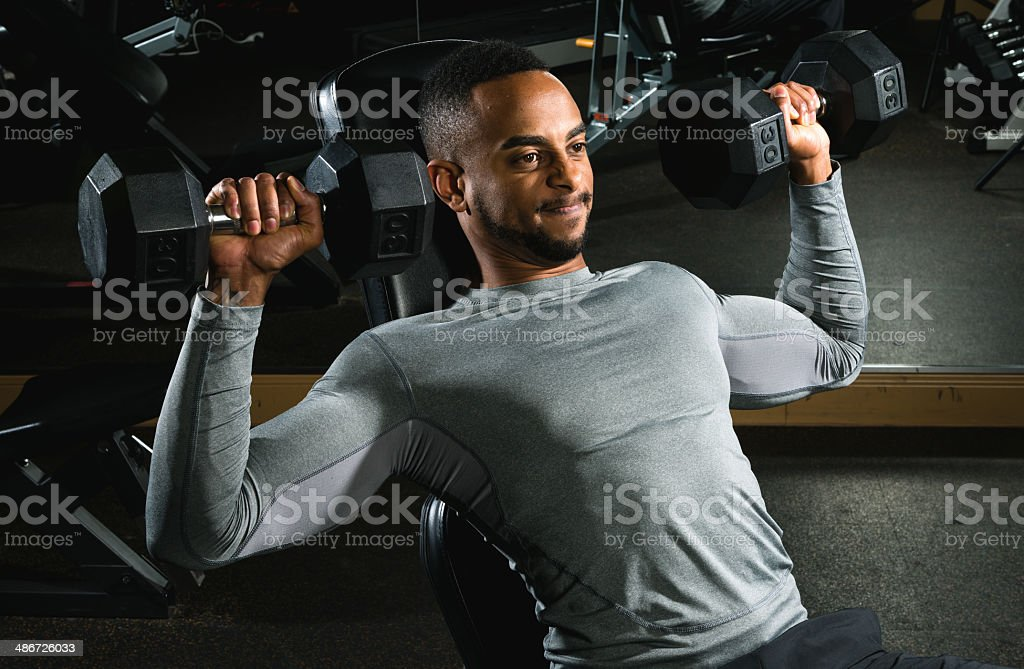 Strong Athletic Man Lifting Free Weights in Gym stock photo