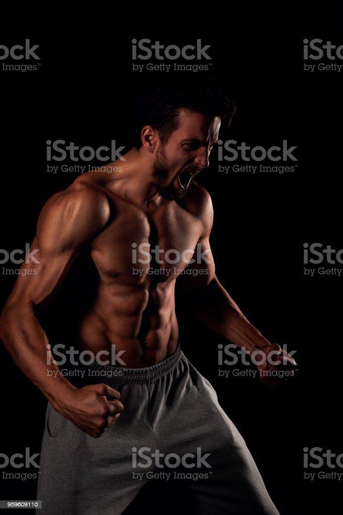 Hombre atlético fuerte haciendo cara enfadada - Foto de stock de Abdomen libre de derechos