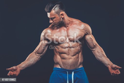 istock strong athletic man on black background 618315862